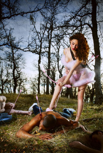 Woman in pink tutu holds bow and arrow over man. Woods in background
